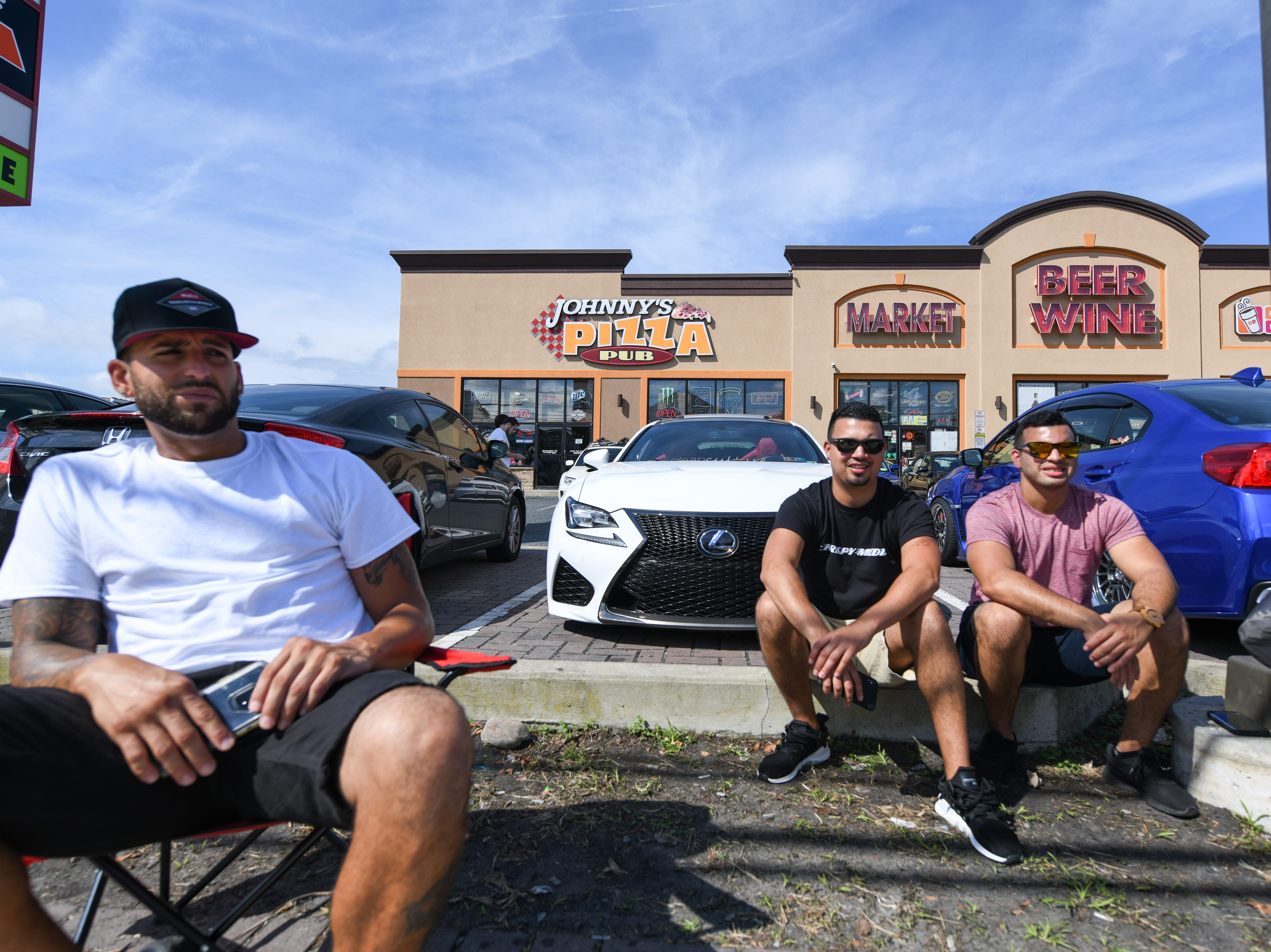 Car owners Robert (middle) and Helson (right) Rivera take a break from driving in front of Johnny's Pizza in Ocean City on Saturday, Sept 29, 2018. The group is in town from Pennsylvania for the unofficial H2Oi weekend, despite the fact that the car show has moved to Atlantic City.