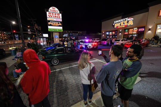 A crowd watches and films as police give out a ticket for driving with lights under the car on Friday, Sept 28, 2018. Popular car show H2Oi  was traditionally held nearby and though it has now moved to Atlantic City attendees continue to flock to Ocean City.