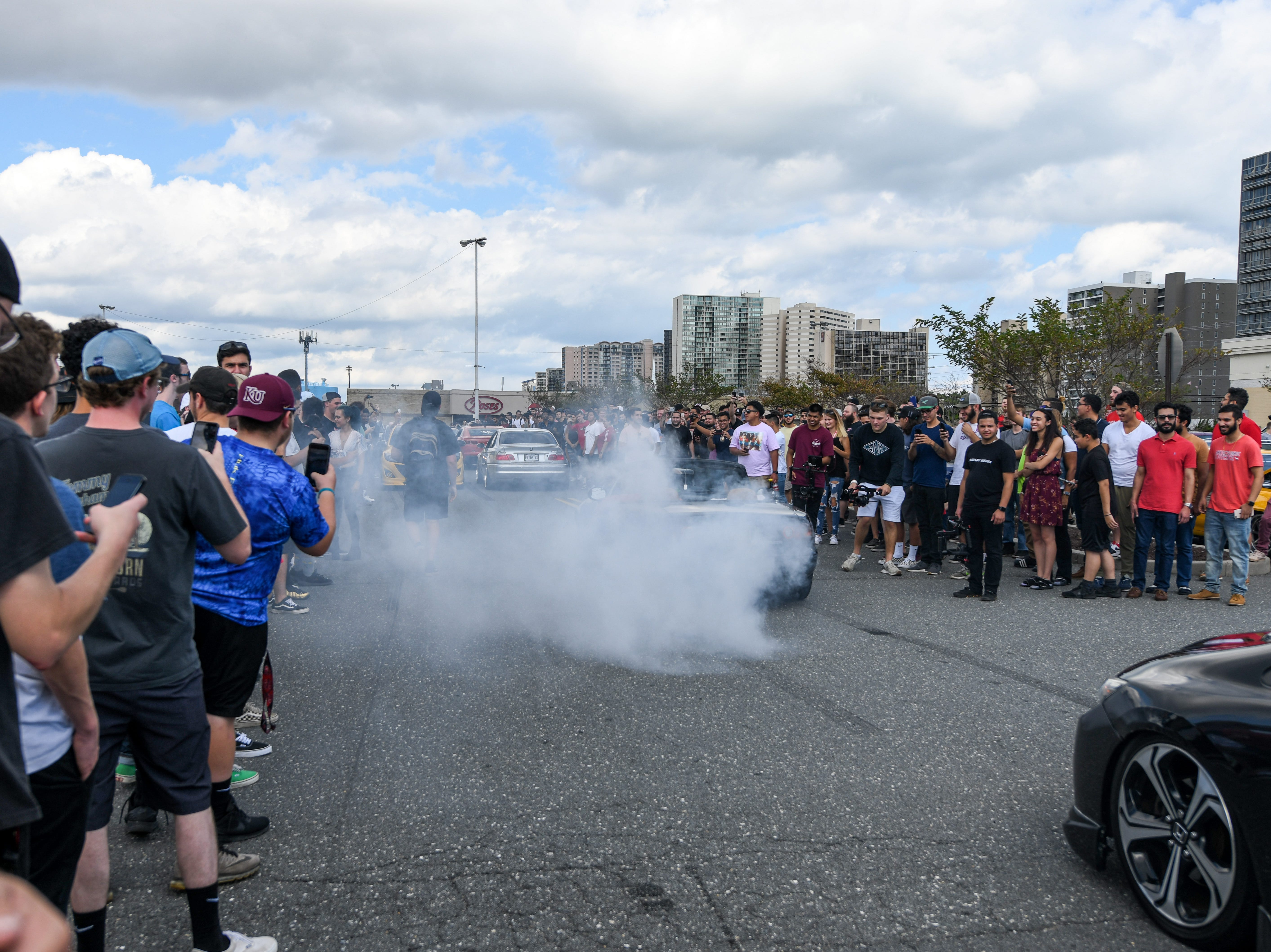 A crowd films and cheers as passing cars perform burnouts in the ACME parking lot on Saturday, Sept 29, 2018. Streets in the area were full of crowds and cars for the unofficial H2Oi weekend, despite the fact that the car show has moved to Atlantic City.
