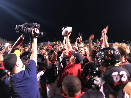The Parkway Panthers celebrate with the game ball from legendary sportscaster Bob Griffin following Saturday's victory against Airline.