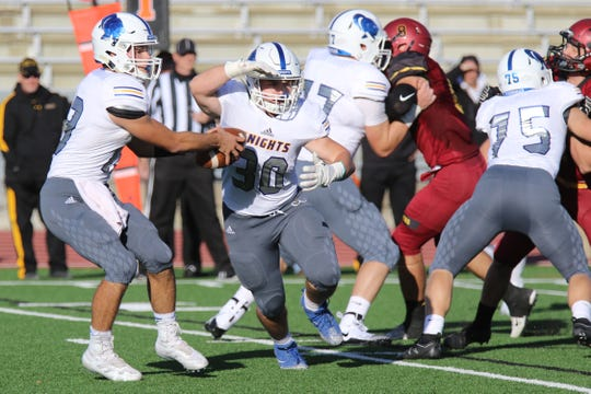 QB #13 Zach Norton fakes the hand off to #30 Tate Wishard prior to throwing a pass during Friday's game at Howard Wood Field.