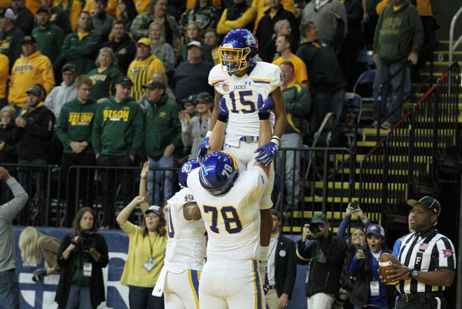 South Dakota State's Cade Johnson (15) gets hoisted into the air be teammate Evan Greeneway to celbrate Johnson's touchdown during the first quarter of the Jackrabbits' matchup against North Dakota State Saturday afternoon at the Fargodome in Fargo.