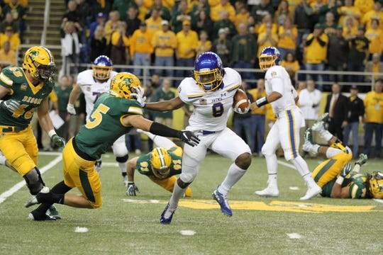 South Dakota State's C.J. Wilson (8) gives a stiff arm to North Dakota State's Robbie Grimsley during the first quarter of the Jackrabbits' matchup against the Bison Saturday afternoon at the Fargodome in Fargo.