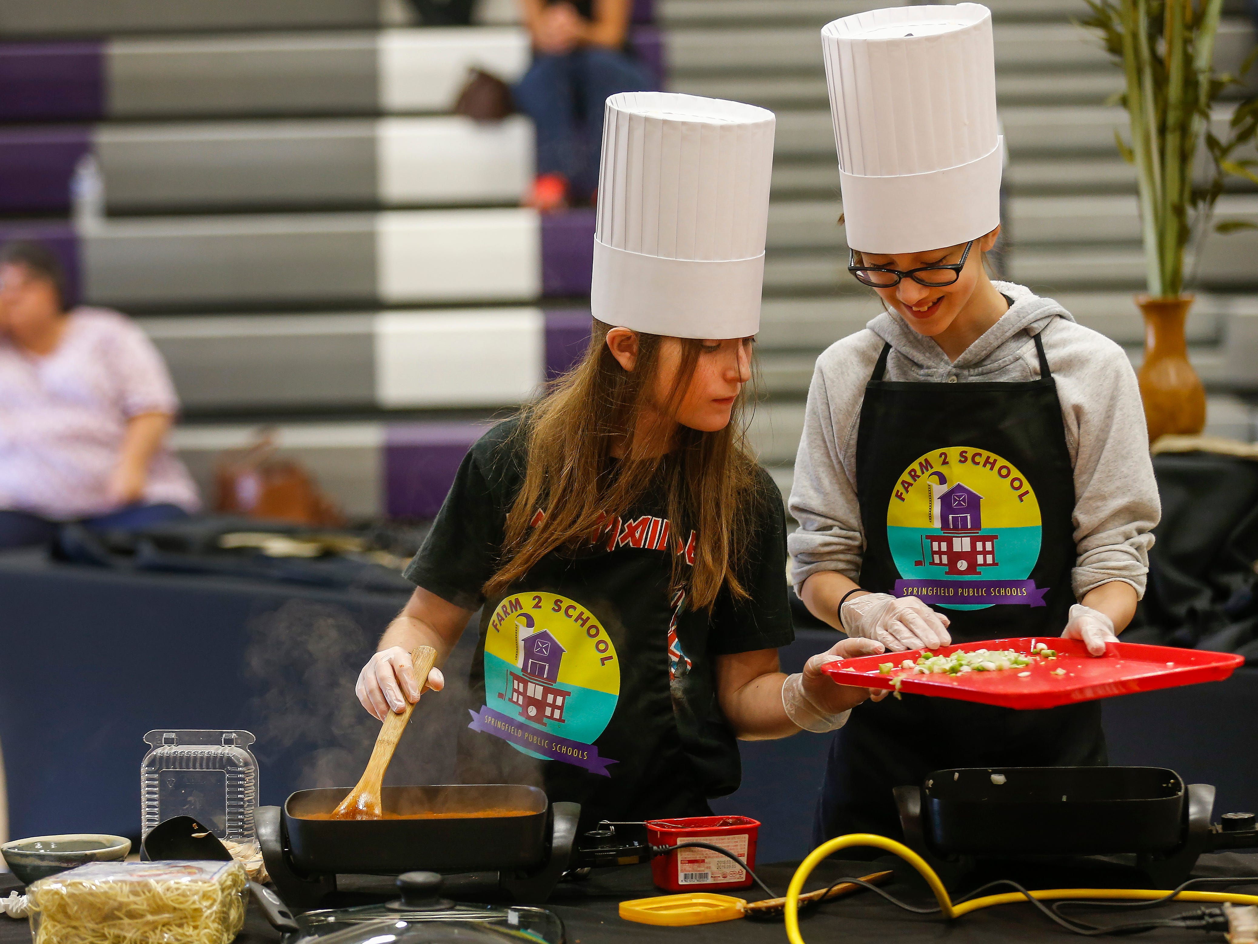 Sage Wilson, left, and Danielle McCorison, students at Central Scholars, prepare their dish during the third annual Junior Chef Competition at Hickory Hills Middle School on Saturday, Sept. 29, 2018.