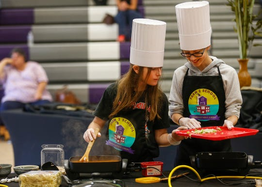 Sage Wilson, left, and Danielle McCorison, students at Central Scholars, prepare their dish during the third annual Junior Chef Competition at Hickory Hills Middle School on Saturday.