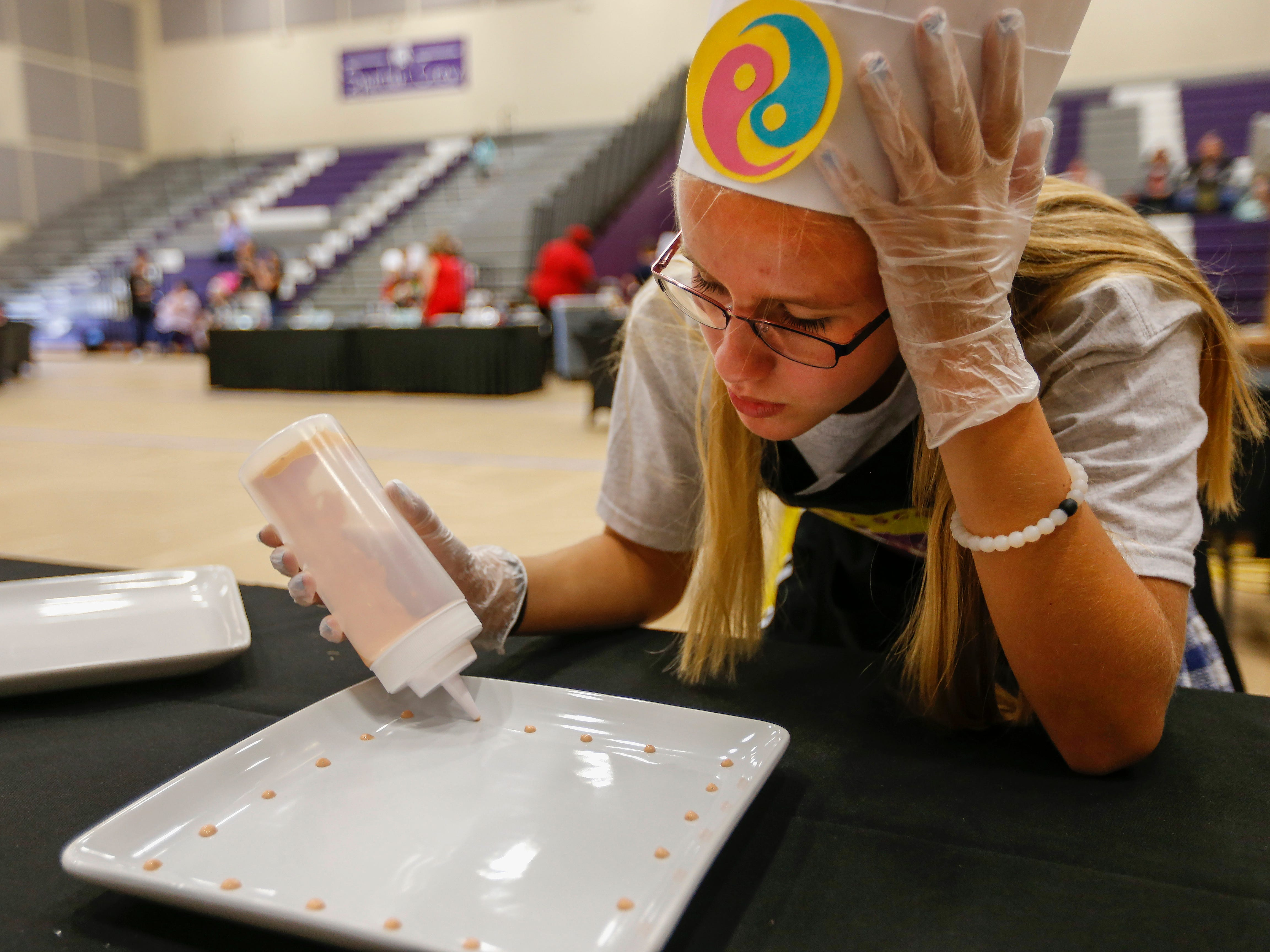 Samantha McCormick, a student at Hickory Hills Middle School, decorates her team's plate during the third annual Junior Chef Competition at Hickory Hills Middle School on Saturday, Sept. 29, 2018.
