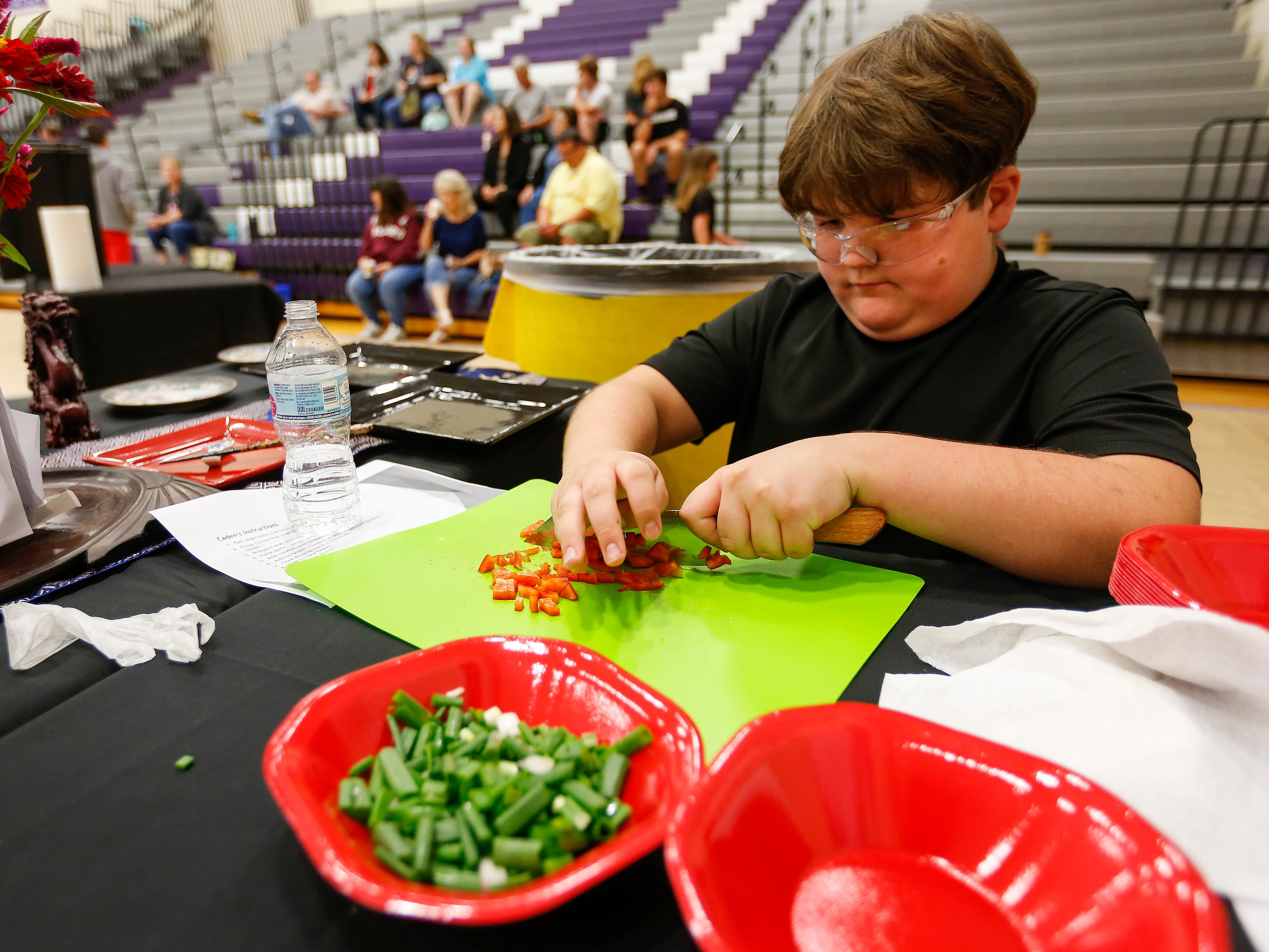 Caden McGeorge, a student at Hickory Hills Middle School, dices peppers during the third annual Junior Chef Competition at Hickory Hills on Saturday, Sept. 29, 2018.