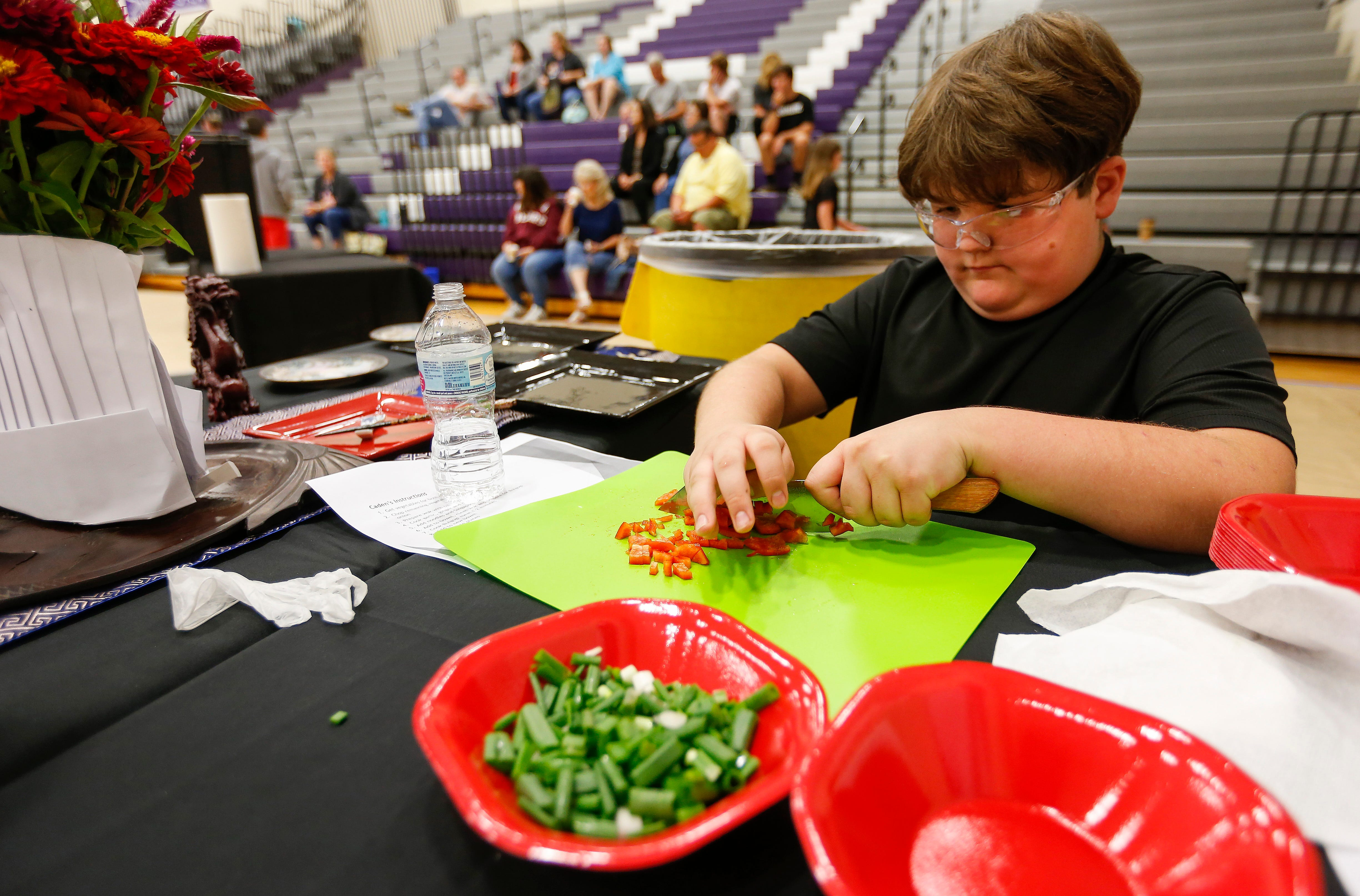 Caden McGeorge, a student at Hickory Hills Middle School, dices peppers during the third annual Junior Chef Competition at Hickory Hills on Saturday.