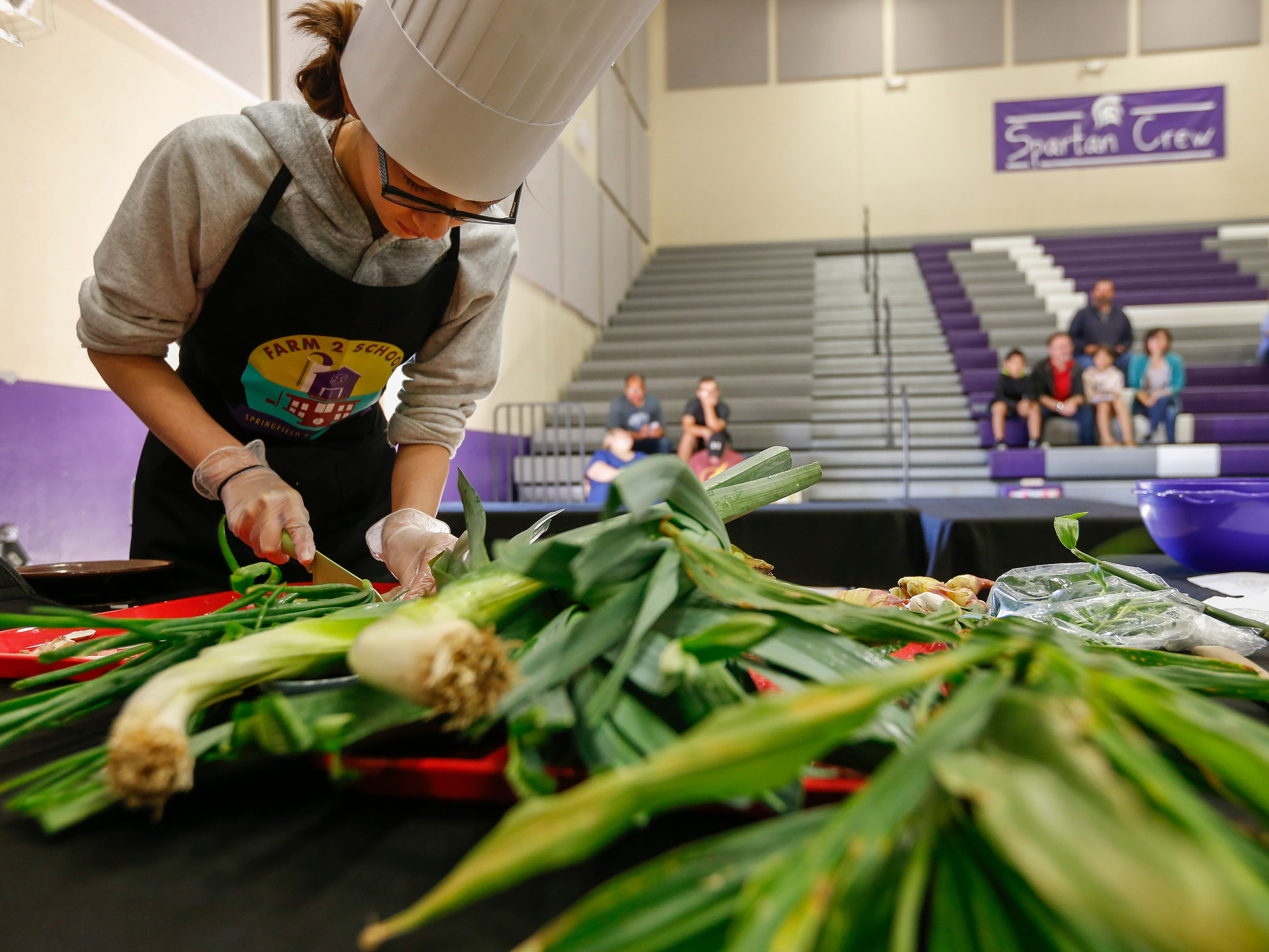 Danielle McCorison, a student at Central Scholars, chops green onions during the third annual Junior Chef Competition at Hickory Hills Middle School on Saturday, Sept. 29, 2018.