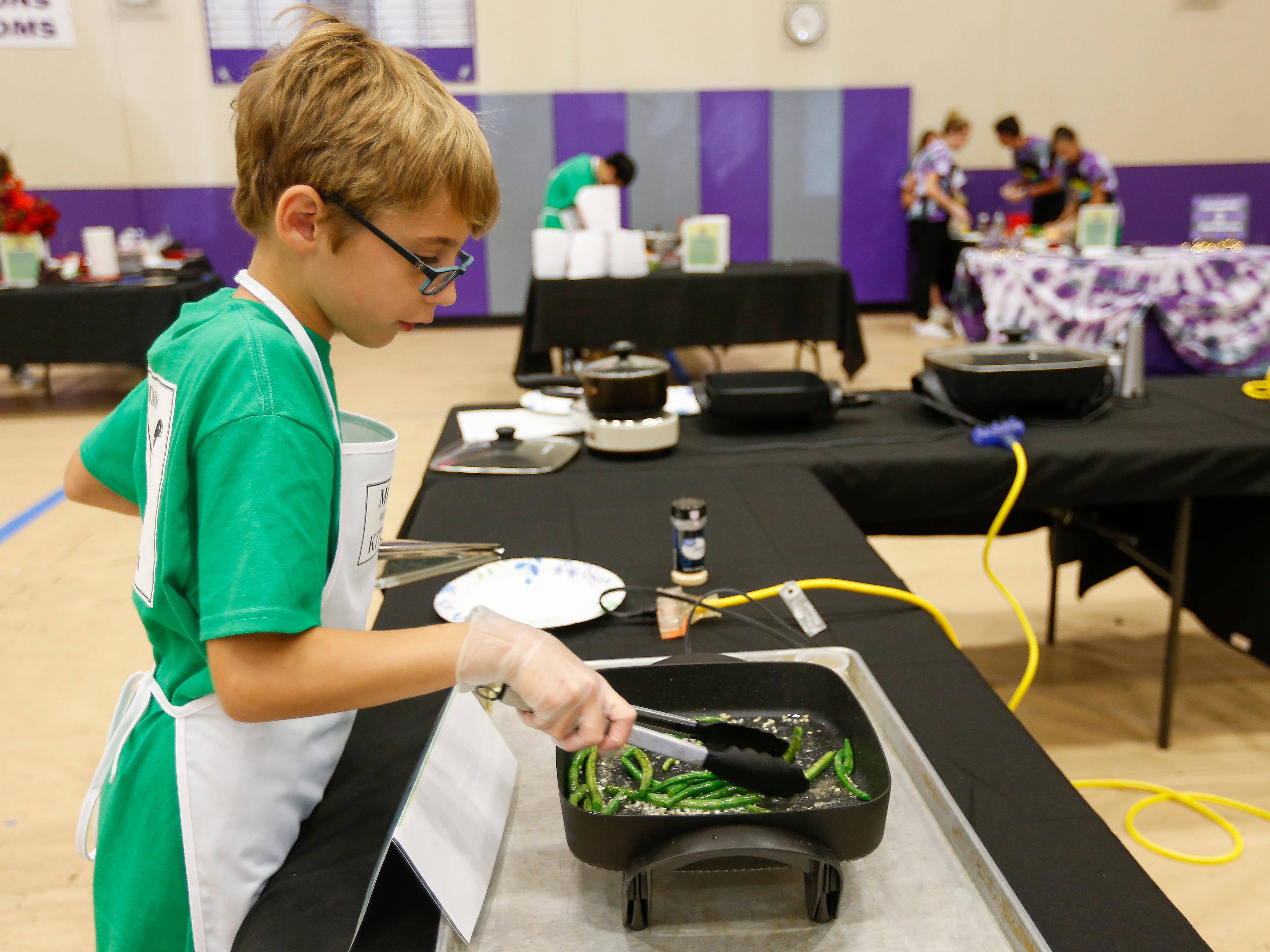 Ryan McDaniel, a student at Cherokee Middle School, sautes green beans during the third annual Junior Chef Competition at Hickory Hills Middle School on Saturday, Sept. 29, 2018.