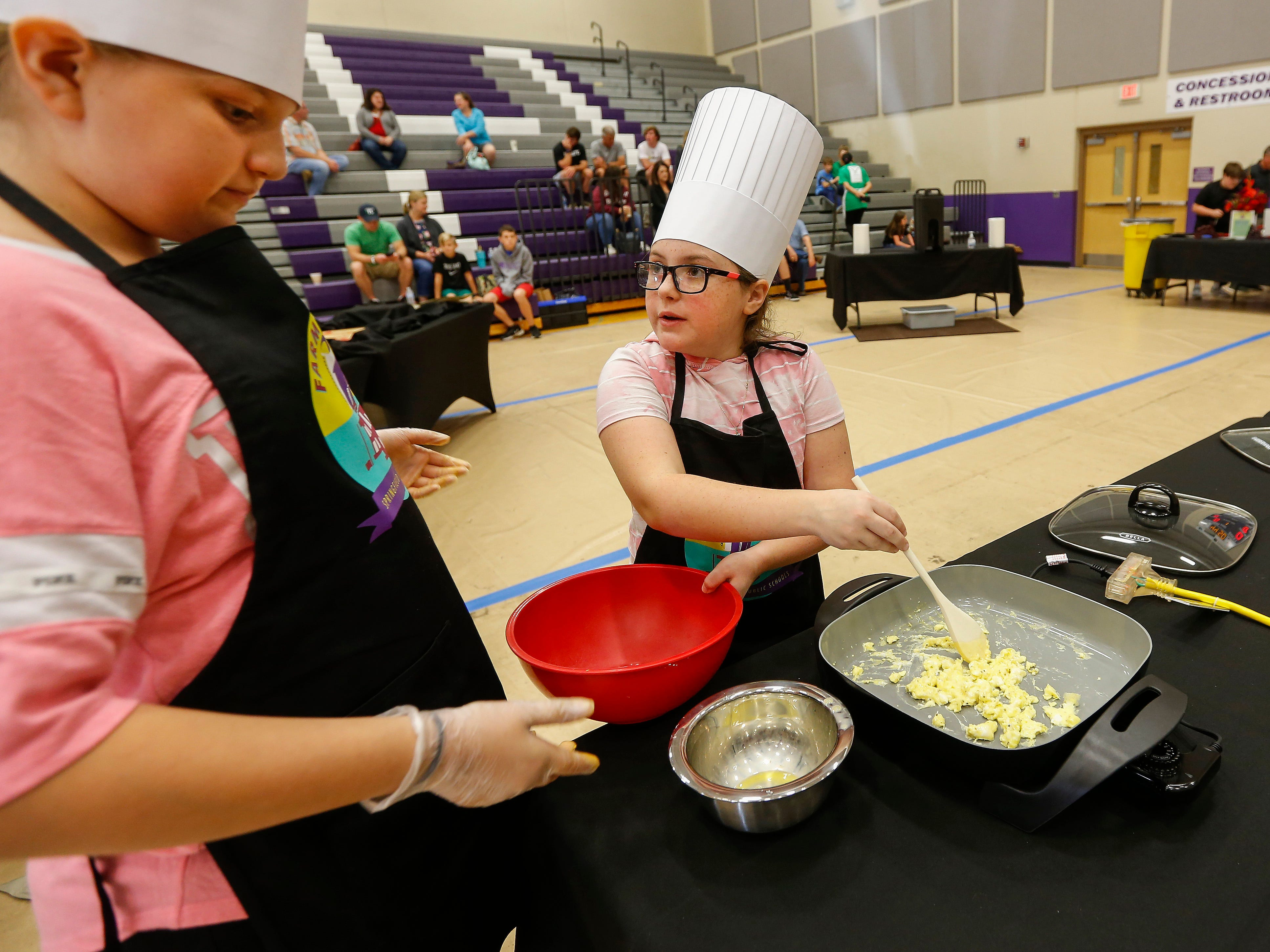 Bryn Eacret, right, takes a bowl from her teammate Addyson Stormzand while scrambling eggs during the third annual Junior Chef Competition at Hickory Hills Middle School on Saturday, Sept. 29, 2018.