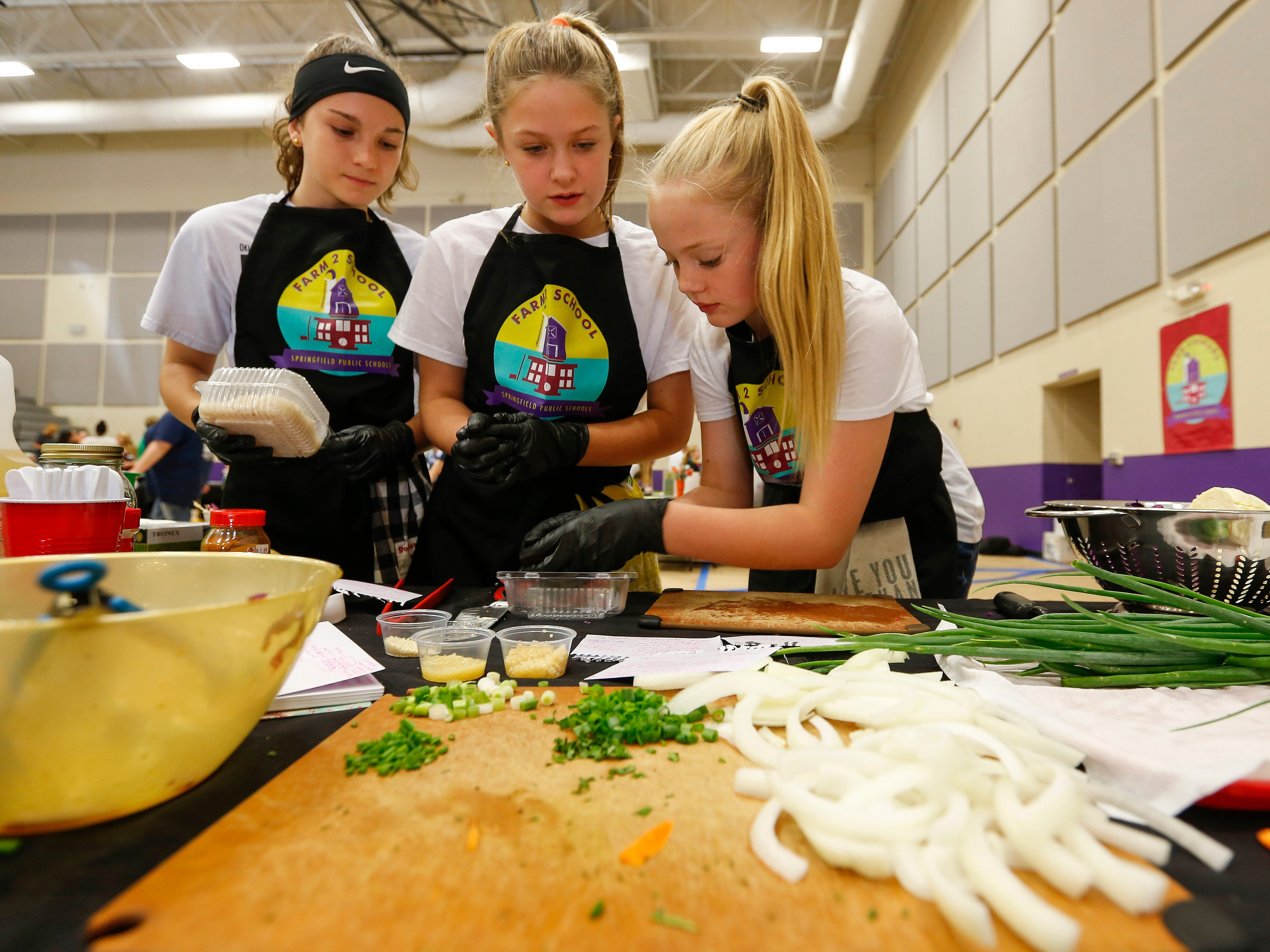 From left, Brooke Chaffin, Delaney Sisney and Kennedy Norman, students at Cherokee Middle School, prepare their dish during the third annual Junior Chef Competition at Hickory Hills Middle School on Saturday, Sept. 29, 2018.