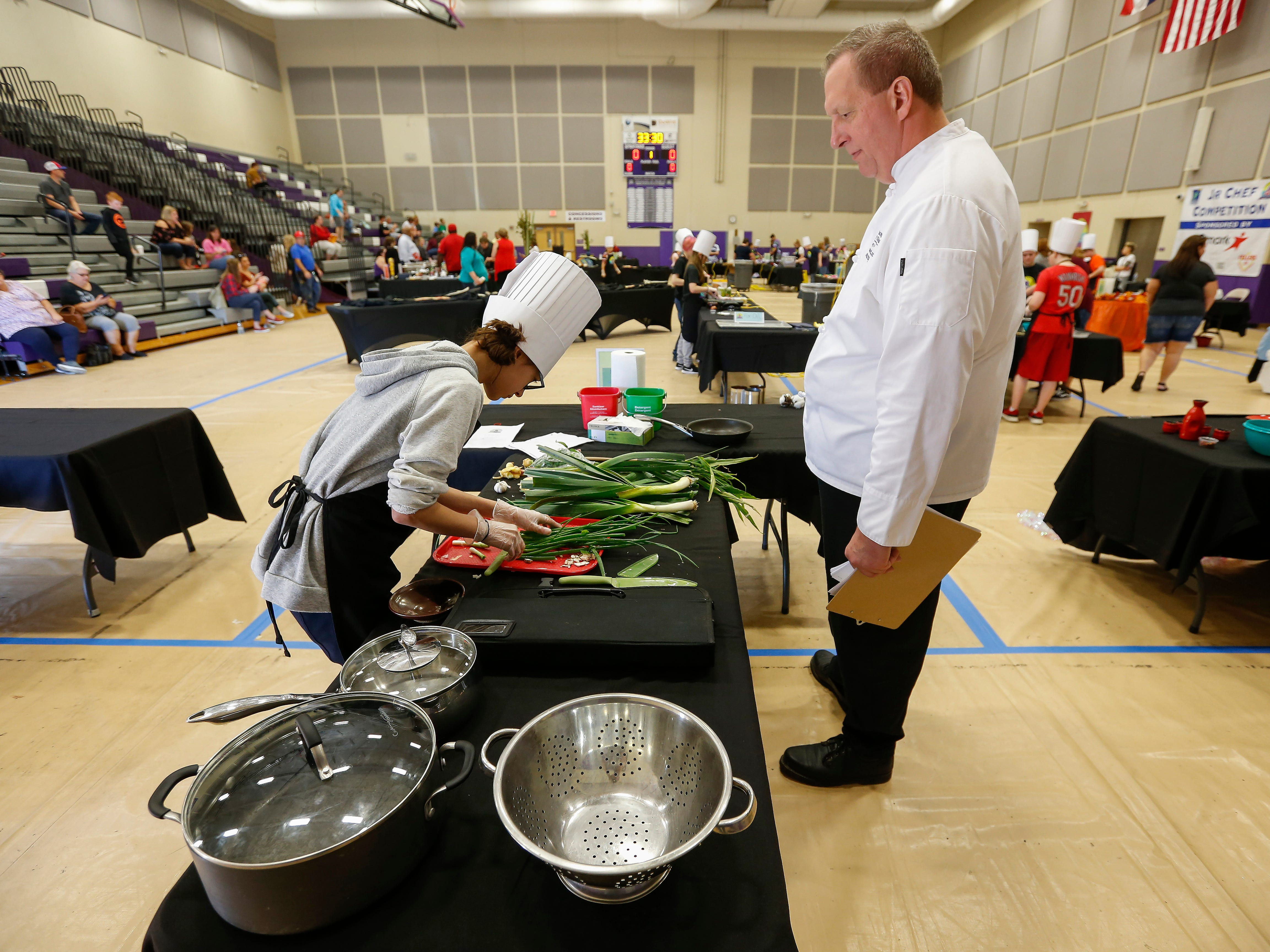 Judge Jeff Ward watches as Danielle McCorison, a student at Central Scholars, chops green onions during the third annual Junior Chef Competition at Hickory Hills Middle School on Saturday, Sept. 29, 2018.