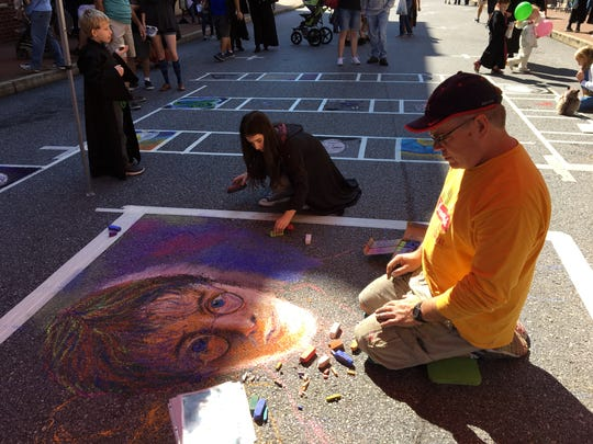 Robert Mott does a chalk drawing of Harry Potter during the third annual Queen City Mischief & Magic festival in downtown Staunton on Sept. 29, 2018. The festival was held from Sept. 28 through 30.