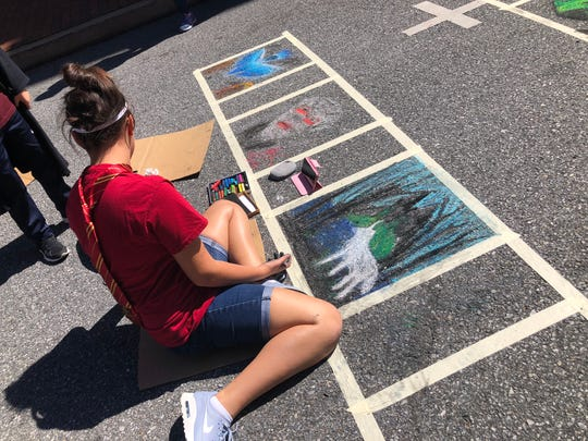 Dasha Milligan of Gainesville, Virginia draws with chalk during the third annual Queen City Mischief & Magic festival in downtown Staunton on Sept. 29, 2018. The festival was held from Sept. 28 through 30.