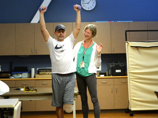 Chris Craig works with weights during physical therapy with Amy Mumbauer, MPT, at Augusta Health on Wednesday, Sept. 26.