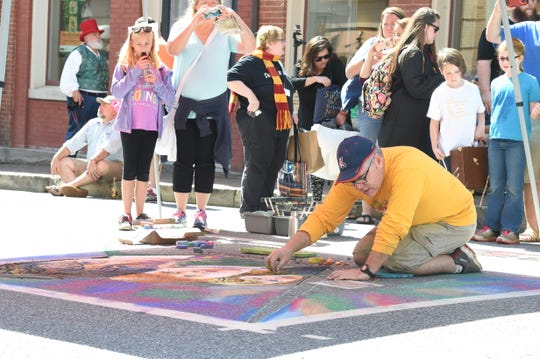 Robert Mott works on a drawing inspired by a Harry Potter movie still during the second day of the  Queen City Mischief & Magic in downtown Staunton, Va., Saturday, Sept. 28, 2018.