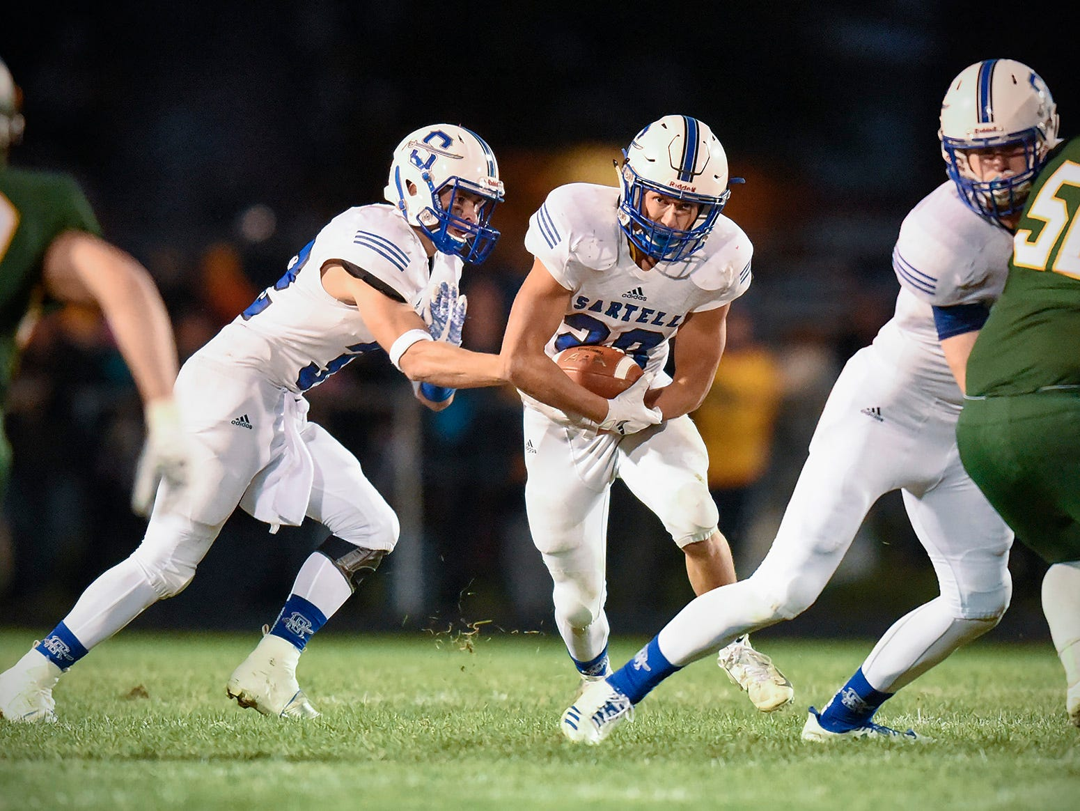 Sartell quarterback Ryan Giguere hands the ball to Cody Neitzke during the first half Friday, Sept. 28, in Sauk Rapids.
