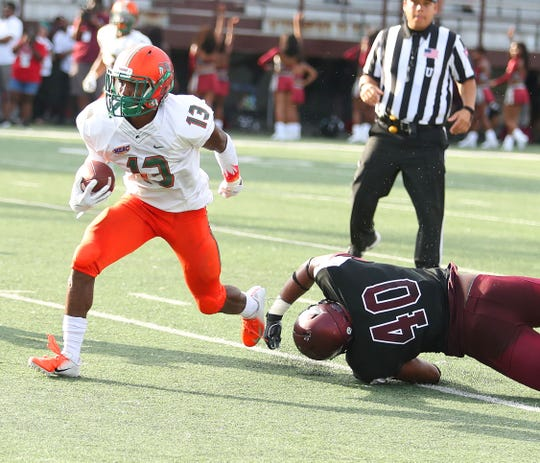 FAMU running back Bishop Bonnett dodges by North Carolina Central linebacker Patrick Conner.