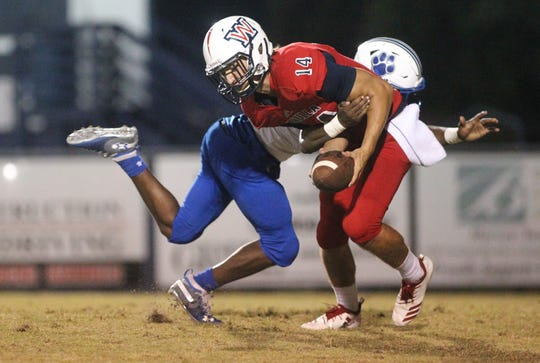 Godby's Quandre Ray tackles Wakulla punter Hunter Busen, who fumbles following a fumbled snap as Godby beat Wakulla 37-13 on Friday night.