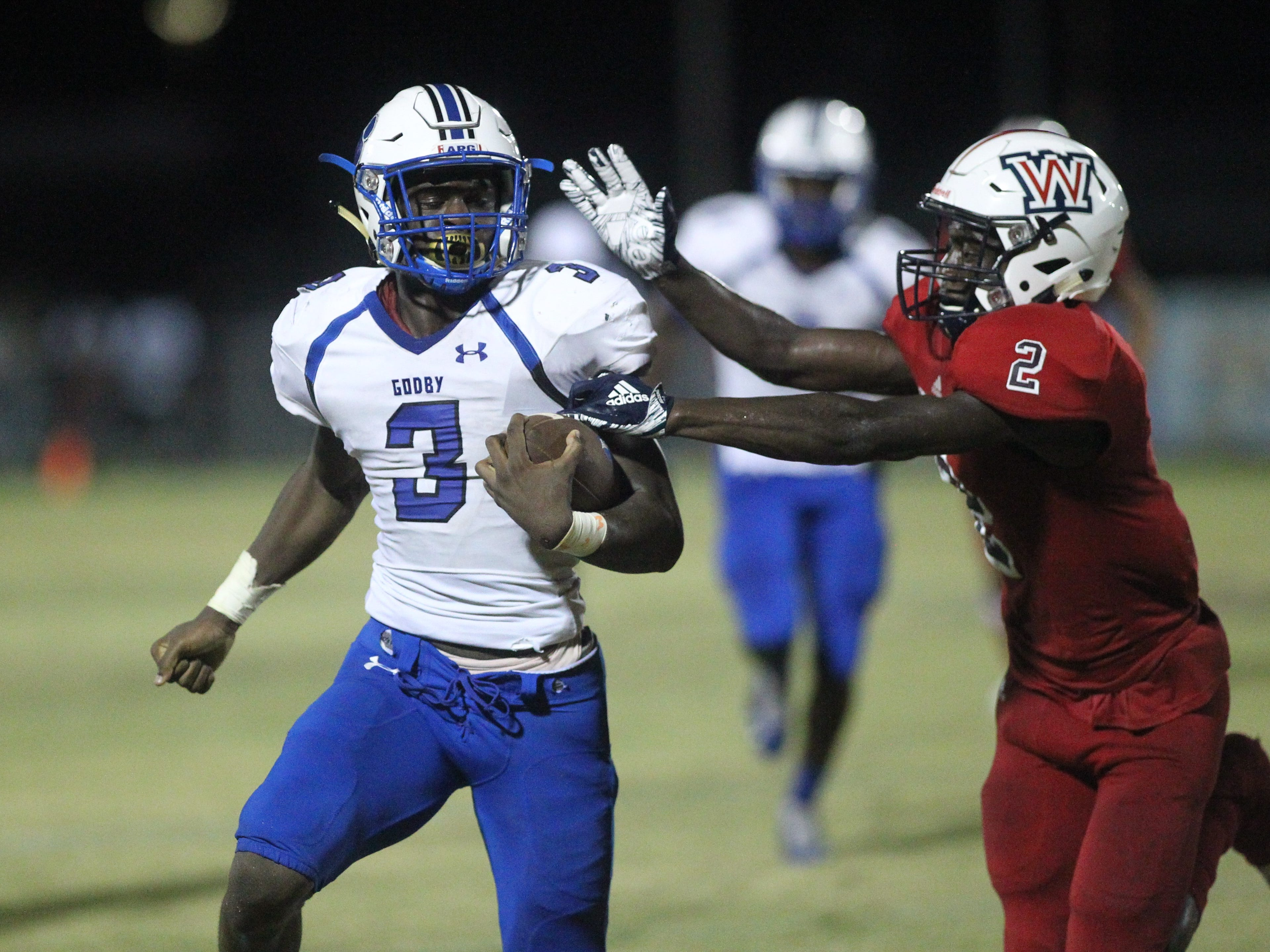Godby running back Jaquez Yant tries to avoid a tackle by Wakulla's Jeremy Harvey as the Cougars beat Wakulla 37-13 on Friday night.