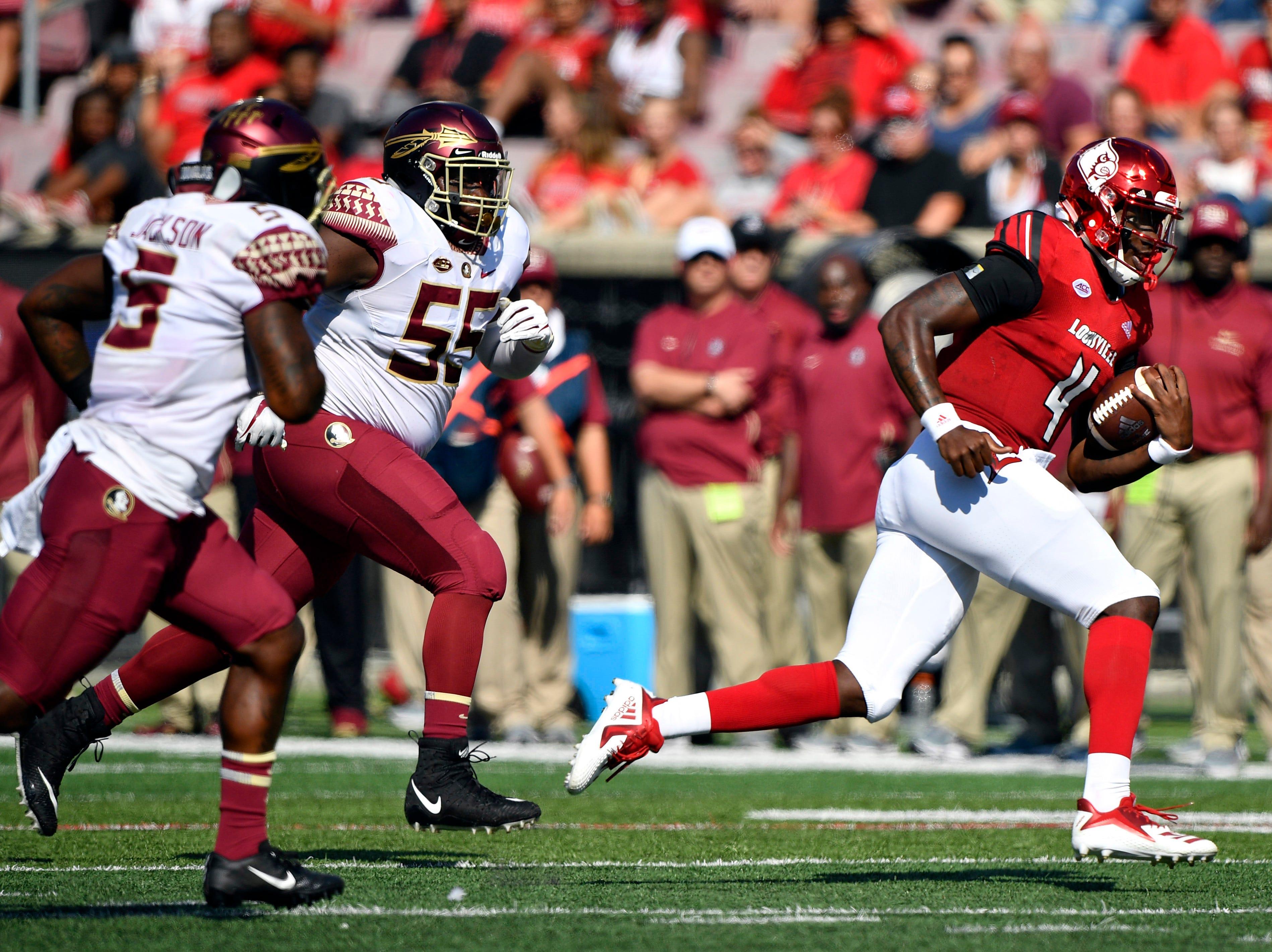 Louisville Cardinals quarterback Jawon Pass (4) runs the ball past Florida State Seminoles defensive tackle Fredrick Jones (55) during first quarter at Cardinal Stadium.