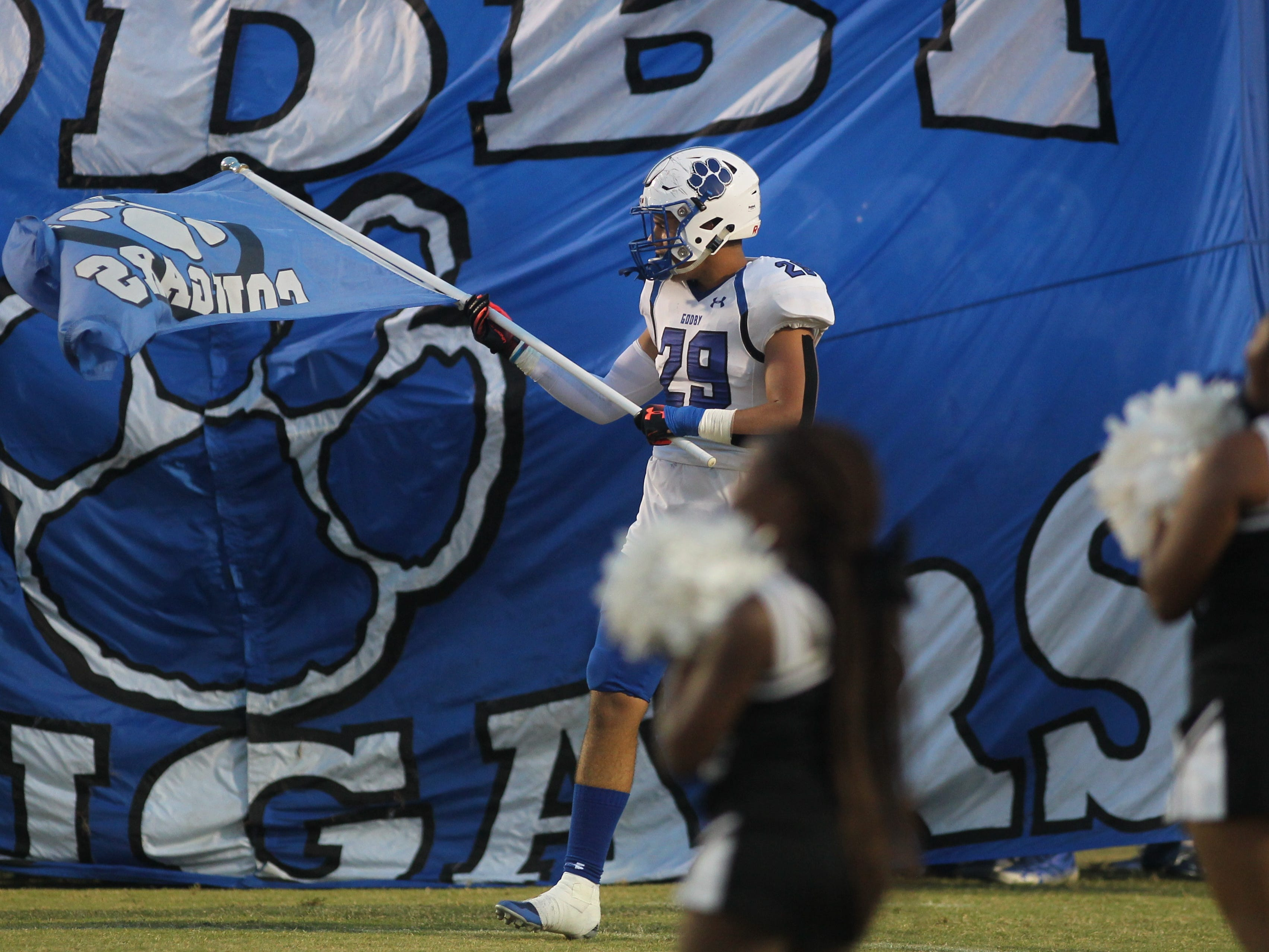 Godby's Kyler Laing waves a flag before leading his team onto the field as Godby beat Wakulla 37-13 on Friday night.