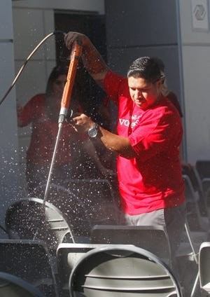 Rudy Alaniz uses a power sprayer to hose down chairs as volunteers from local Wells Fargo Banks help beautify the Boys & Girls Club of Simi Valley on Saturday as part of the 29th annual United Way of Ventura County Day of Caring.