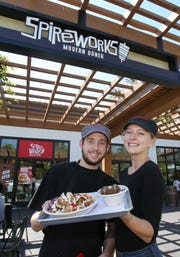 Alex Cutsforth and Savanna Gann hold  up a Berlin-style rice bowl and beef falafels at the new SpireWorks in Thousand Oaks.