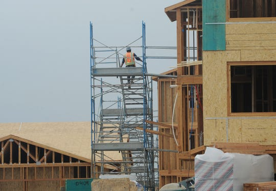 A worker navigates some scaffolding at an apartment project under construction near Springville Drive and W. Ponderosa Drive in Camarillo.