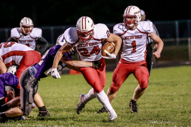 Medford's Garrett Hill(24), middle, avoids being tackle by Mosinee's Adam Maurer(22) Friday, Sept. 28, 2018, during Great Northern Conference boys football game at Mosinee High School football field in Mosinee, Wis. Next Hill is Ean Wilson(1).