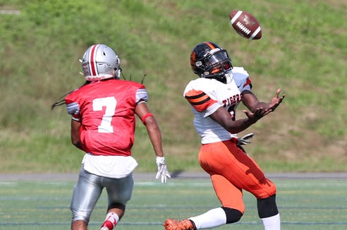 White Plains' Josiah Harris (8) catches a pass in front of Yonkers' Nuryel Benitez (7)  that set up White Plains' first touchdown in the first half, during football action at Saunders High School in Yonkers Sept. 29, 2018. White Plains won the game 14-7.