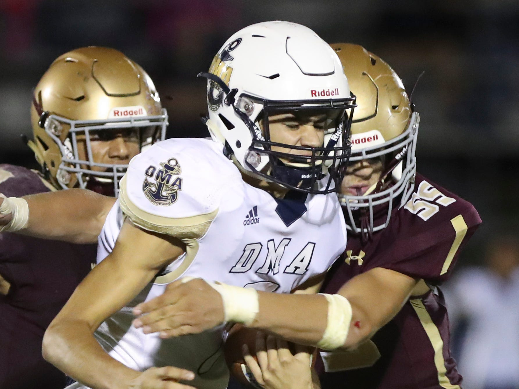 Delaware Military quarterback Joseph Deal is hit after a ground gain by St. Elizabeth's Thomas Zatalava in the third quarter at Baynard Stadium Friday.