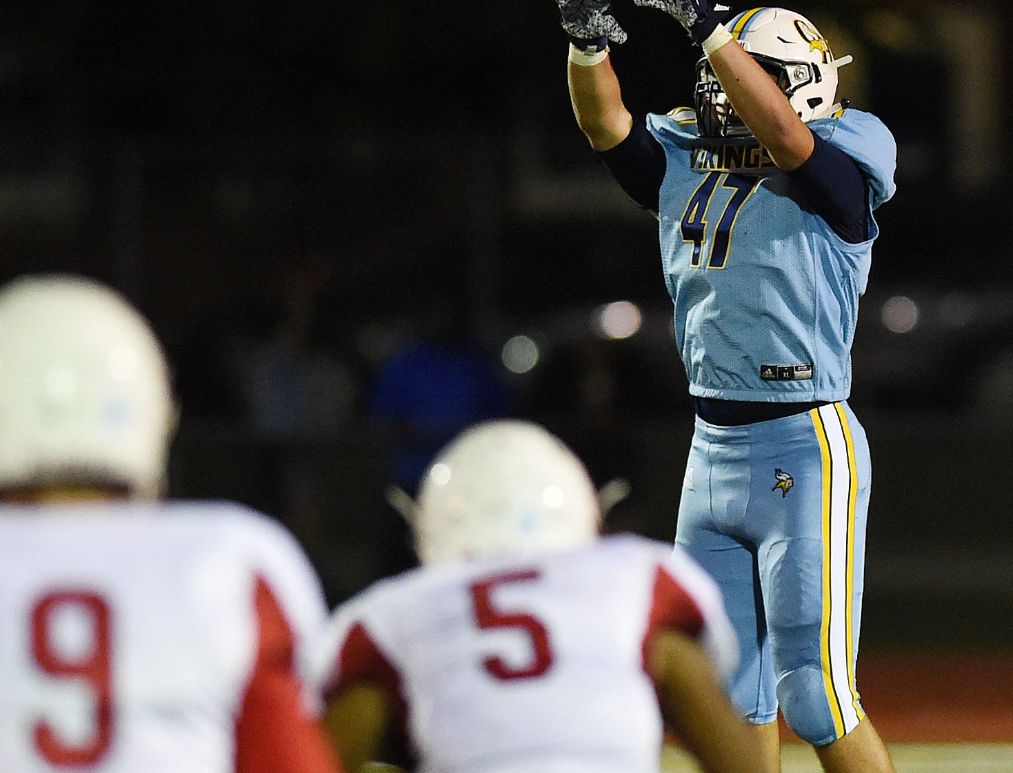 Cape Punter #47 Patrick Tkach jumps for the ball as Cape Henlopen HS (blue) hosted Smyrna HS (red) in Varsity Football in Legends Stadium at the school near Lewes on Friday September 28.