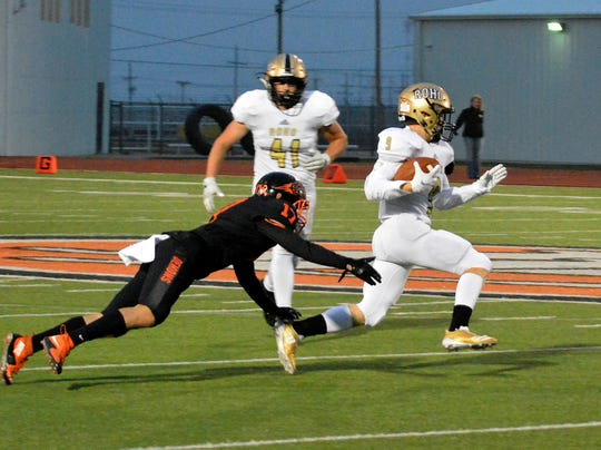 Rider's Jack Hatch runs past Dumas' Damian Orozco (17) Friday, Sept. 28, 2018, in Dumas.