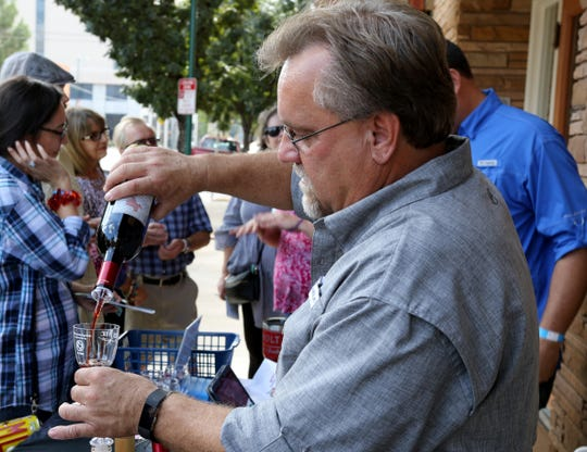 Scott Poenitzsch, Houseshoe Bend Cellars Vineyard and Winery, pours a red wine during the Wichita County Heritage Society Wine & History Walk Saturday, Sept. 29, 2018, in downtown Wichita Falls.