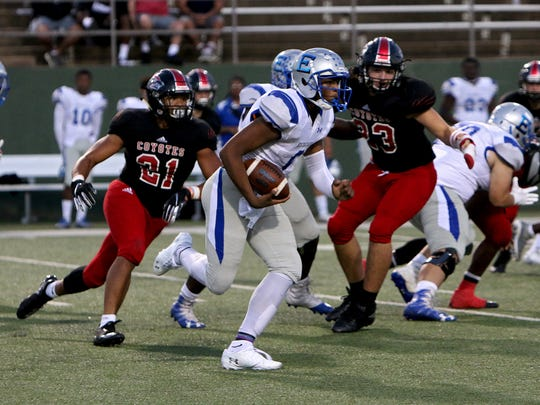 Lubbock Estacado quarterback Jay'Lon Dobbins keeps the ball for a rush as Wichita Falls High defenders Makkedah Brown (21) and Jacob Dollar (23) try to chase after him on Friday, Sept. 28, 2018, at Memorial Stadium.