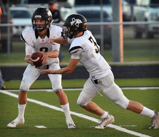 Quanah Indian quarterback Clayton Laughery (2) hands off to his runningback Colton Tole (3) during Friday night's game against the Archer City Wildcats. Archer City defeated Quanah, 27-6.
