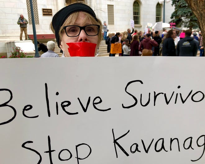 With tape covering her mouth, protester Jane Huhn, 72, of Denver stands silently with a sign showing support for sexual assault  survivors and in opposition to the nomination of federal judge Brett Kavanaugh to the U.S. Supreme Court. Huhn was one of about 200 people who protested outside the offices of Republican Sen. Cory Gardner on Friday afternoon.