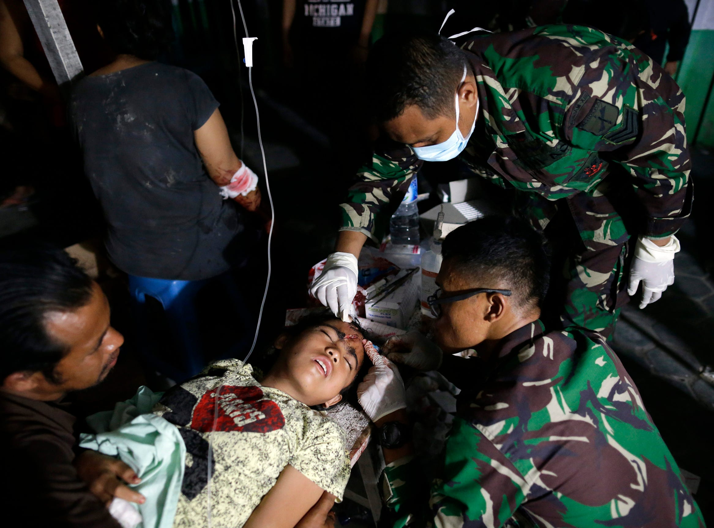 An Indonesian earthquake survivor gets medical treatment outside a military hospital in Palu, Central Sulawesi, Indonesia, on Sept. 29, 2018. According to reports, at least 384 people have died as a result of a series of powerful earthquakes that hit central Sulawesi and triggered a tsunami.