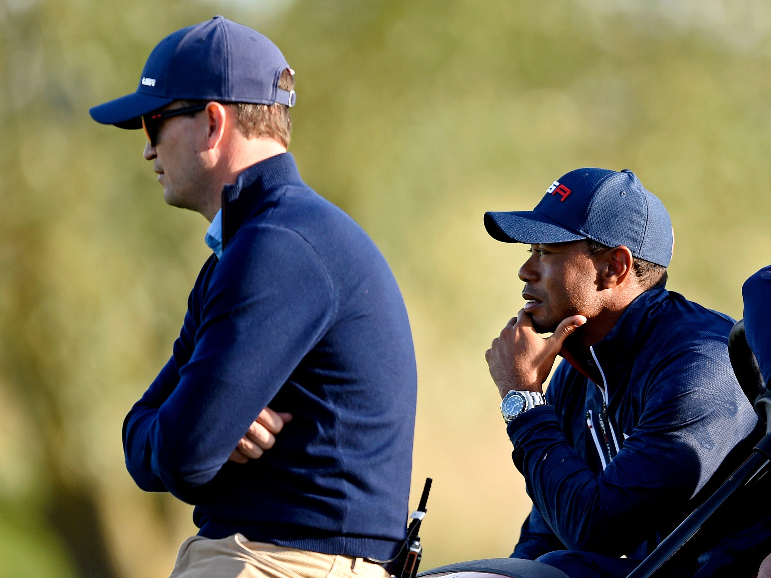 United States vice-captain Zach Johnson and Tiger Woods watch from a golf cart during the Saturday afternoon matches.