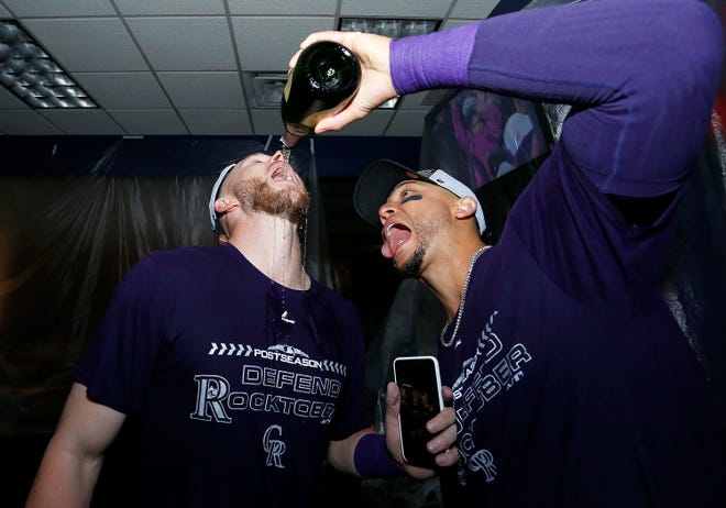 Colorado Rockies outfielder Carlos Gonzalez pours champagne into the mouth of infielder Trevor Story following a win against the Washington Nationals that secured a playoff berth at Coors Field.