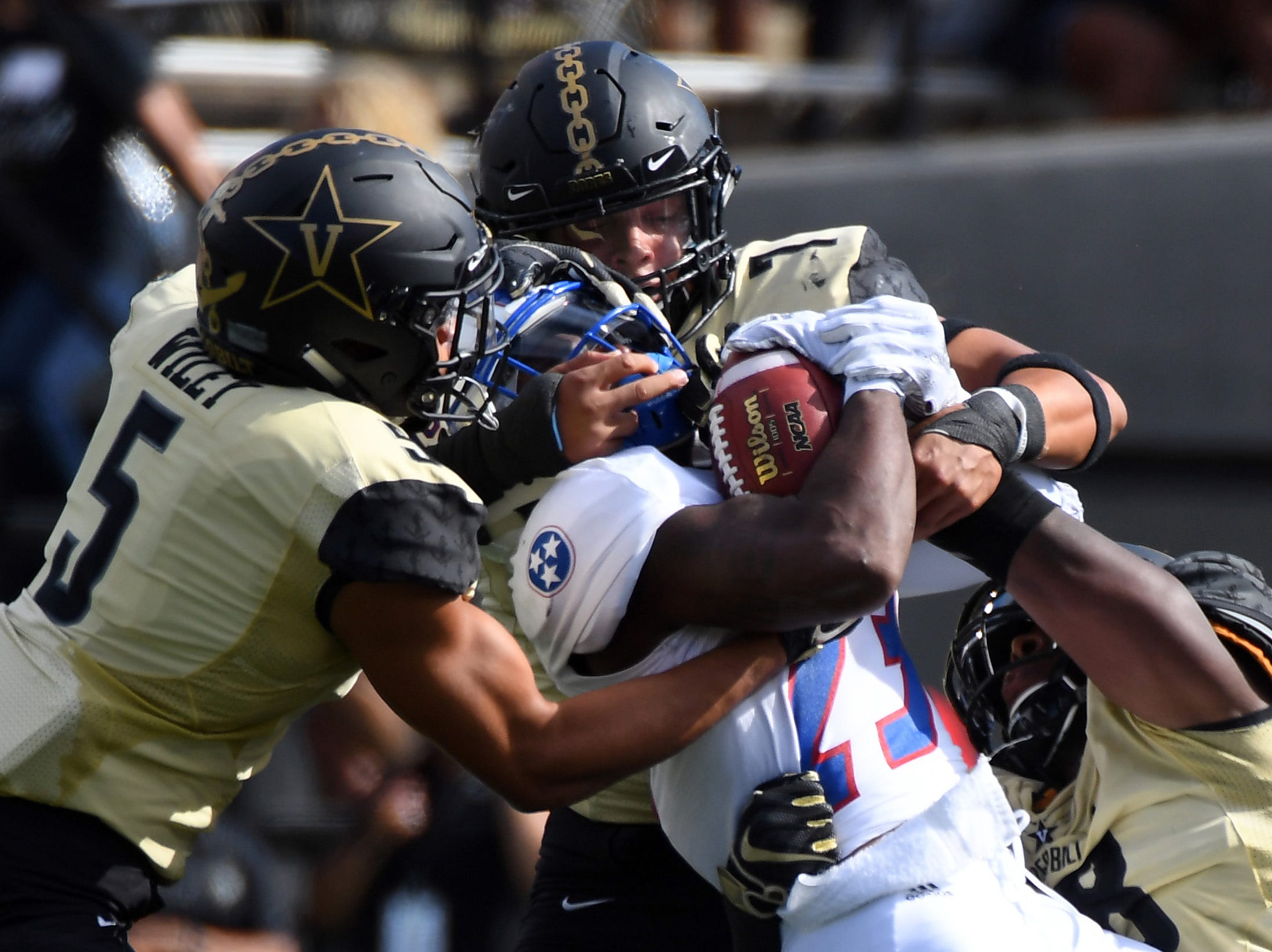 Tennessee State Tigers running back Te'kendrick Roberson (23) is tackled for a loss by a group of Vanderbilt Commodores defenders during the first half at Vanderbilt Stadium.