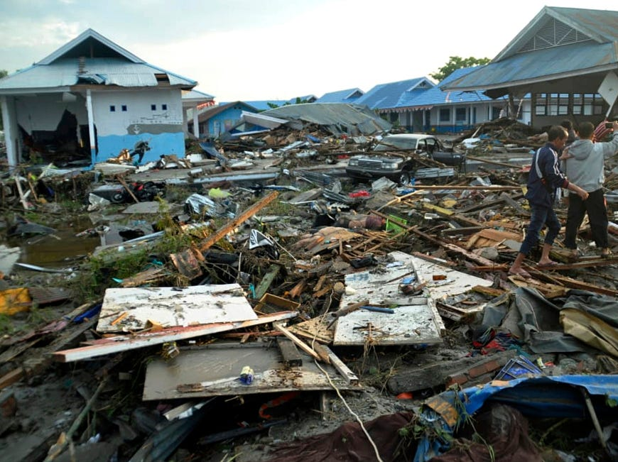 Indonesian men survey the damage following earthquakes and a tsunami in Palui, Indonesia.