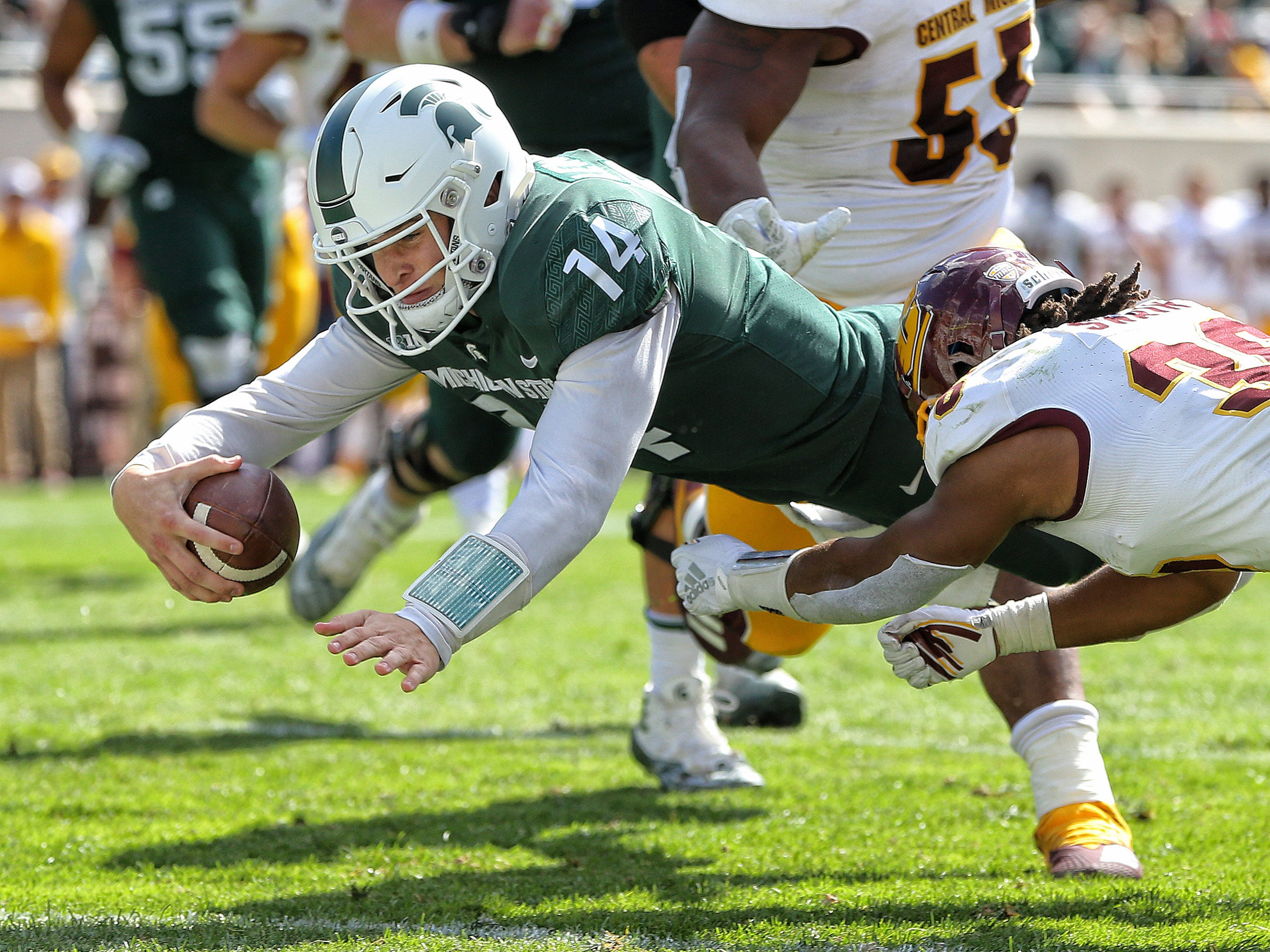 Michigan State Spartans quarterback Brian Lewerke (14) dives into the end zone during the first half against the Central Michigan Chippewas at Spartan Stadium.