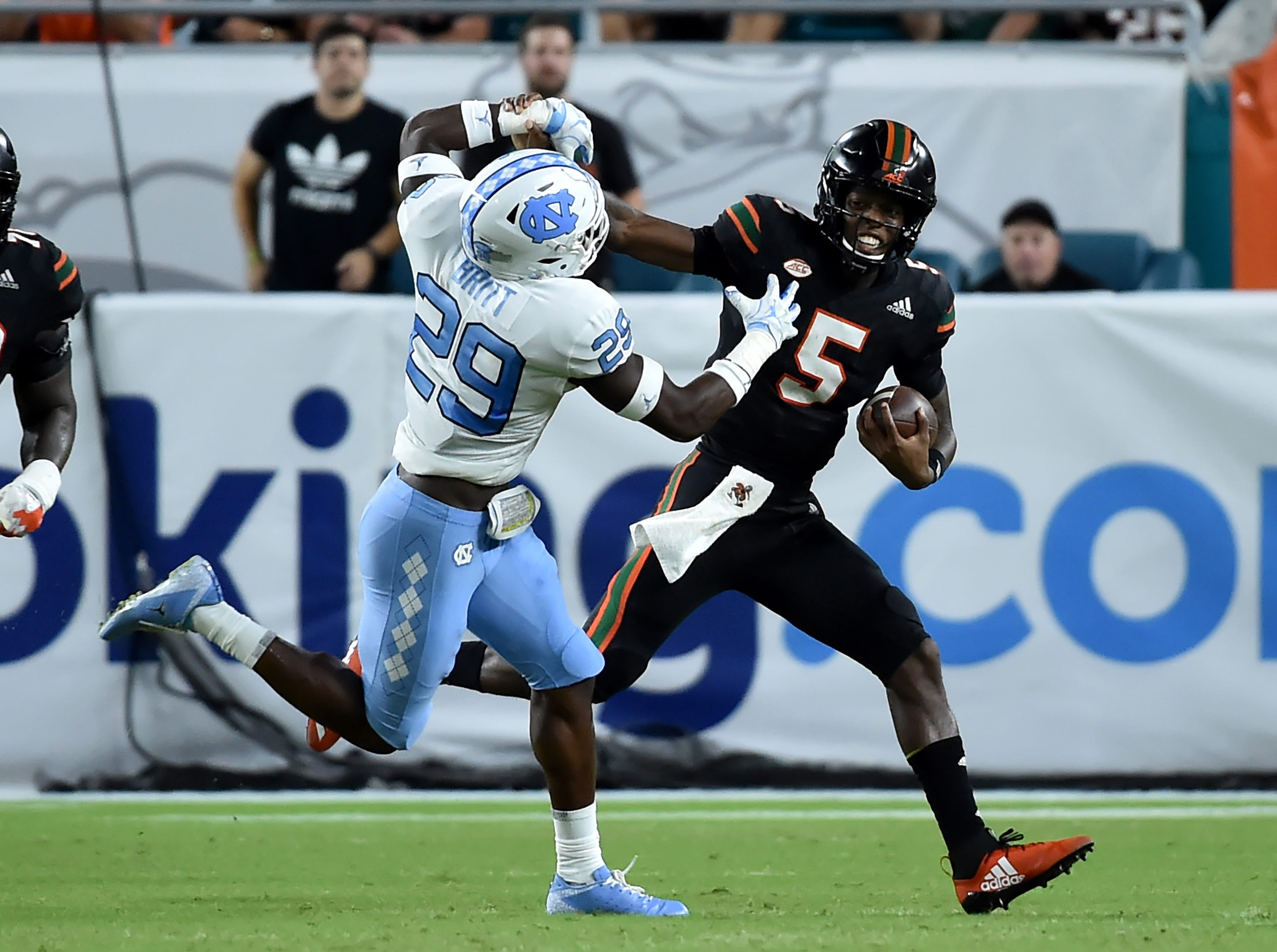 Miami Hurricanes quarterback N'Kosi Perry (5) stiff-arms North Carolina Tar Heels safety J.K. Britt (29) during the second half at Hard Rock Stadium.