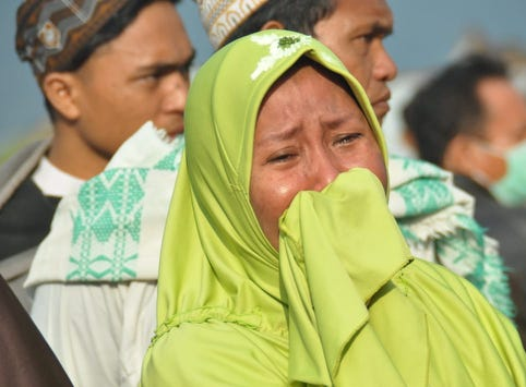A woman cries as people look at the damages after an earthquake and a tsunami hit Palu, on Sulawesi island