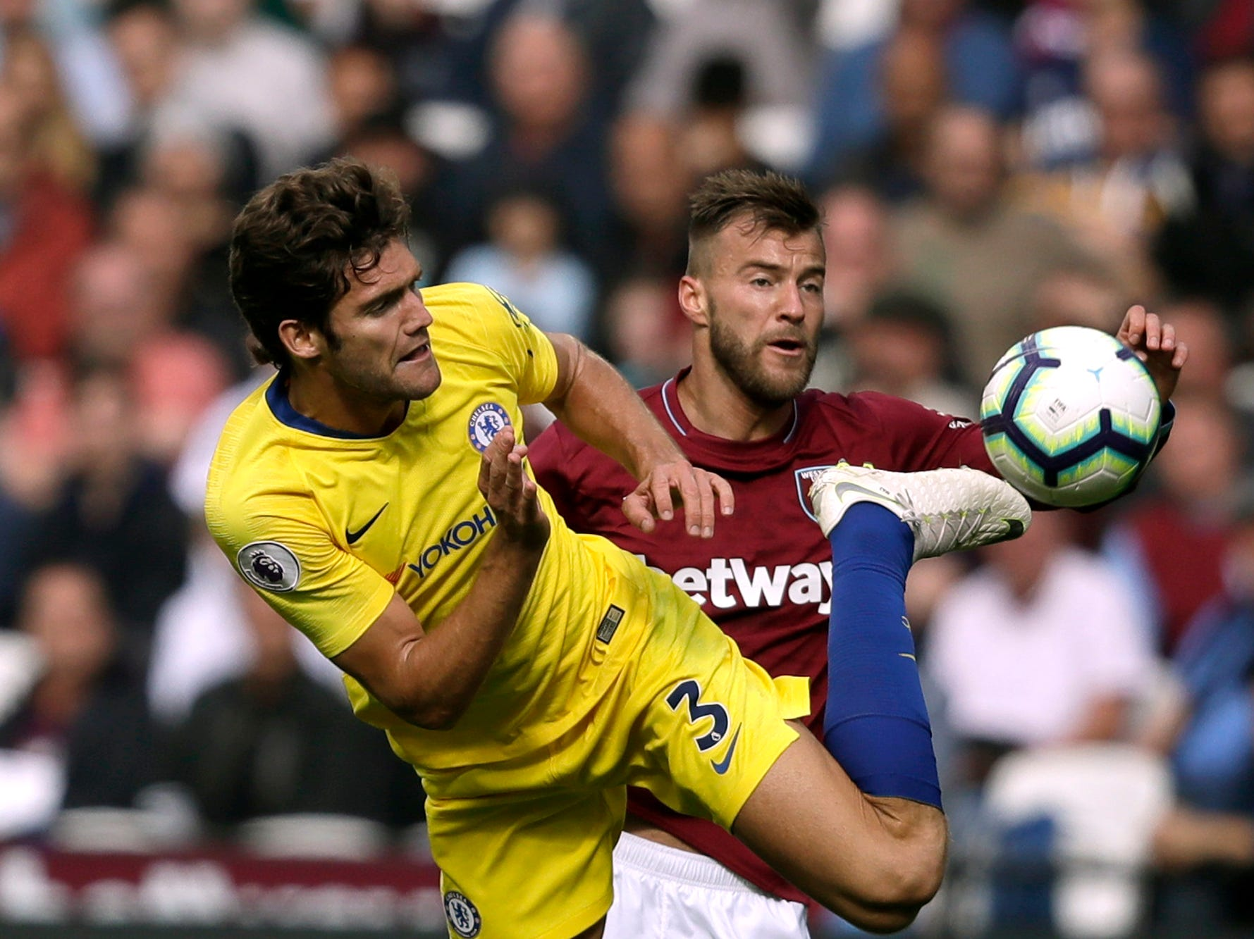 Chelsea's Marcos Alonso, left, vies for the ball with West Ham's Andriy Yarmolenko.