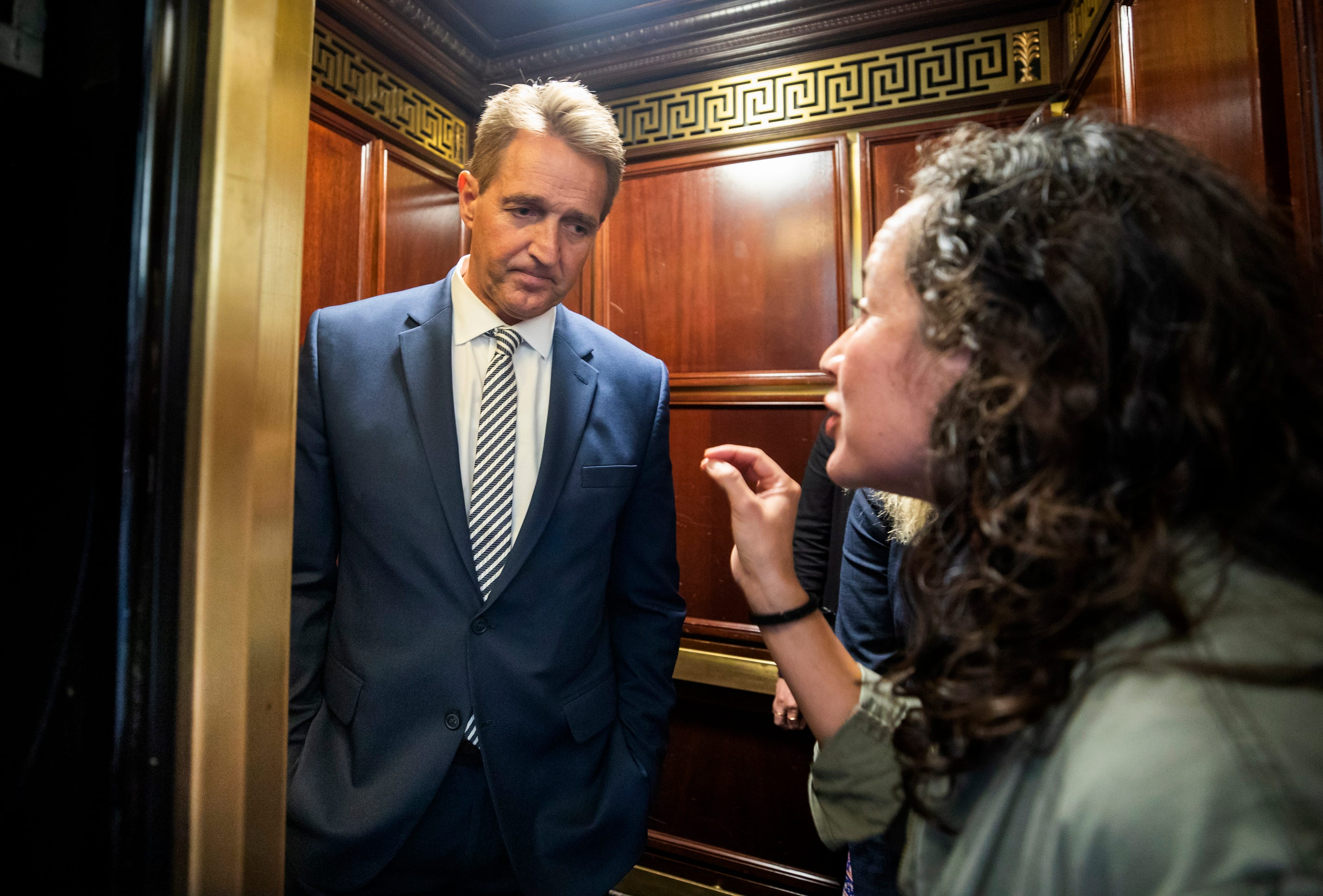 Ana Maria Archila, a survivor of a sexual assault, right, confronts Republican Senator from Arizona Jeff Flake in an elevator after Flake announced that he vote to confirm Supreme Court nominee Brett Kavanaugh in the Russell Senate Office Building in Washington, DC, on Friday.