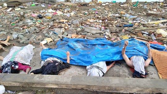En la imagen se observan varios cuerpos sin vida cubiertos con una lona azul.